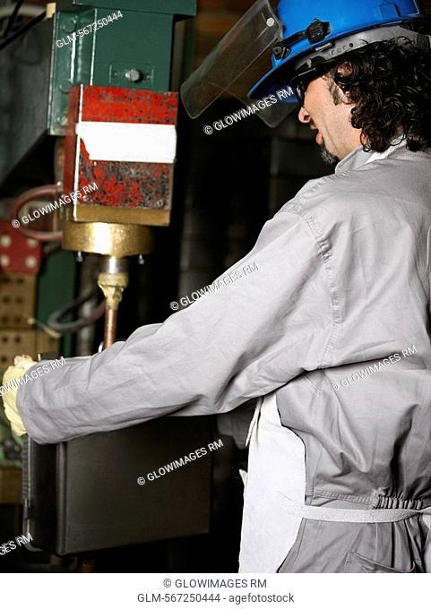Side profile of a manual worker working on a spot welding machine