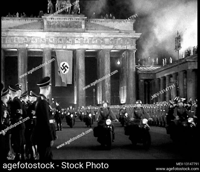 Male German Officers and Soldiers Lining Pariser Platz by the Brandenburg Gate With A German Flag Hanging From It as a Formation of Male Motorbike Riders Pass...
