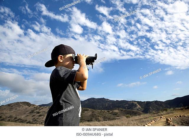 Boy looking out through binoculars, Thousand Oaks, California USA