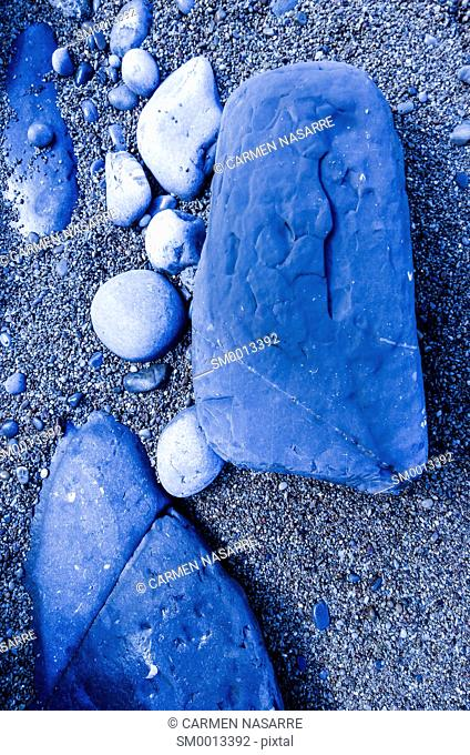 Fragments of rocks of different sizes on sand with tungsten light