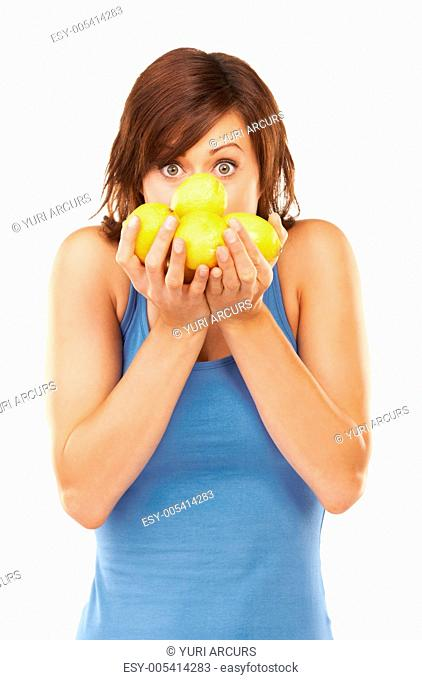 Playful studio portrait of a young woman holding up a bunch of lemons in front of her face isolated on white
