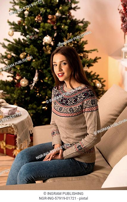 Beautiful woman wearing winter outfit sitting on couch at home near Christmas tree