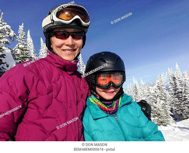 Mother and daughter wearing ski gear outdoors