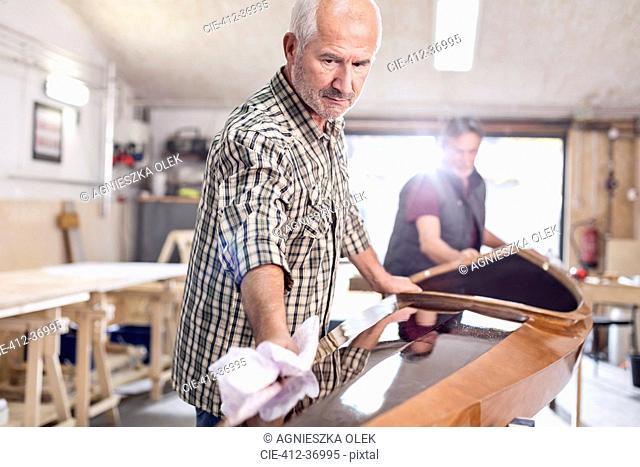 Senior man finishing, wiping wood kayak in workshop