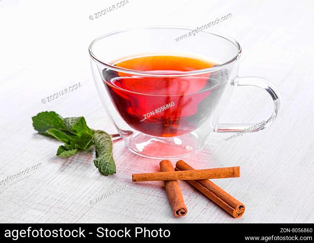 Glass cup of tea on a wooden table with sliced lemon and cinnamon