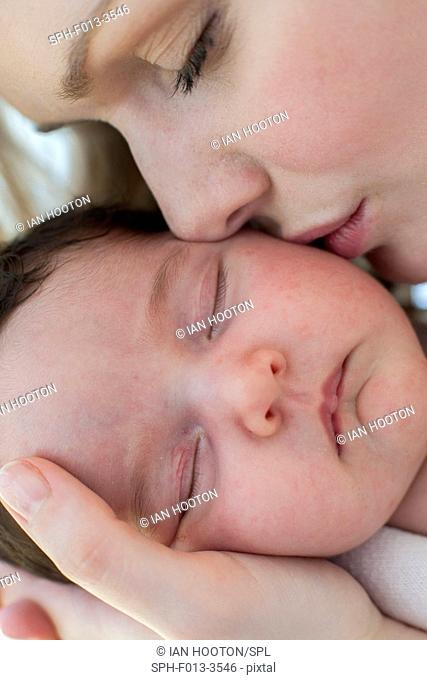 MODEL RELEASED. Mother kissing newborn baby girl