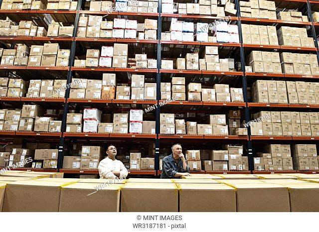 Two male warehouse workers checking inventory in a large distribution warehouse full of products stored in cardboard boxes on pallets on large racks