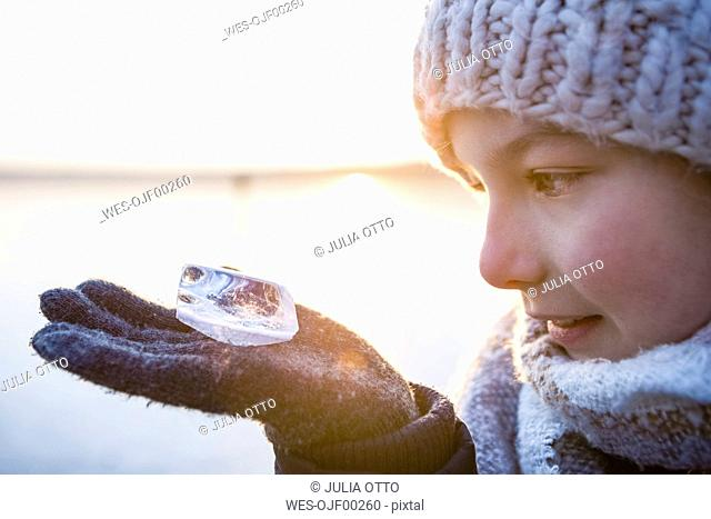 Germany, Brandenburg, Lake Straussee, portrait of a girl standing on frozen lake, looking at piece of ice on her hand