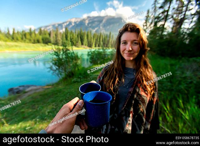 Selective focus of two happy adult people spending time together in a beautiful nature reserved park drinking coffee and tea in camping style cups