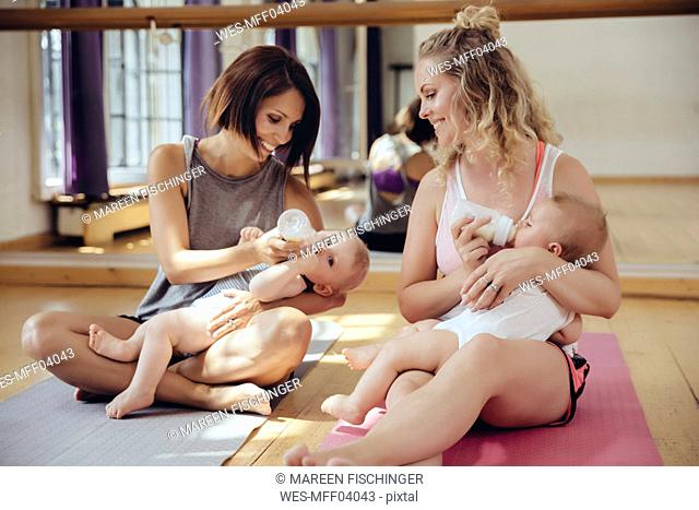 Two mothers bottle-feeding their babies in exercise room