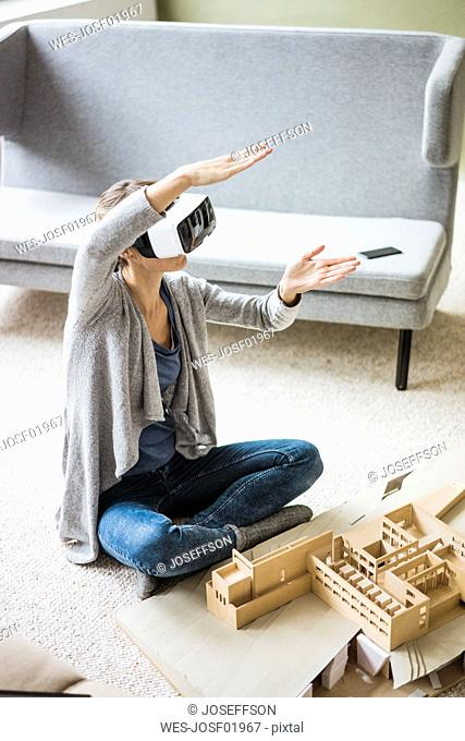 Woman in office with architectural model wearing VR glasses