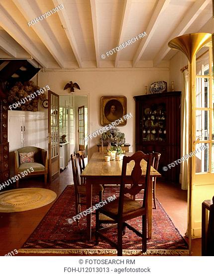 White beamed ceiling in country dining room with antique woodend table and chairs
