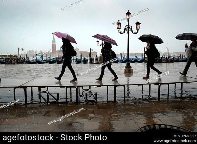 Tourists carrying umbrellas march along a temporary walkway to keep their feet dry during floods at St Mark's, Venice