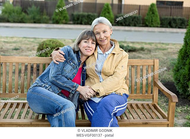 Portrait of senior woman sitting together with her adult daughter on a bench