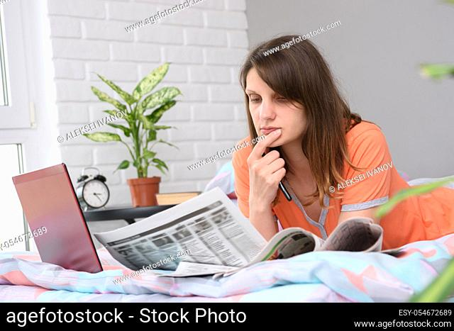 Girl thoughtfully reads with job offers announcements
