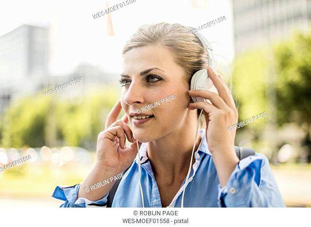 Portrait of smiling woman in the city wearing headphones