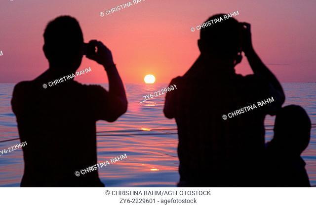 Photographing sunrise. Dolphin watch sunrise tour, Cala Ratjada, Mallorca, Balearic islands, Spain in July
