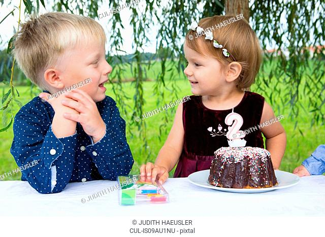 Boy and female toddler with birthday cake in garden