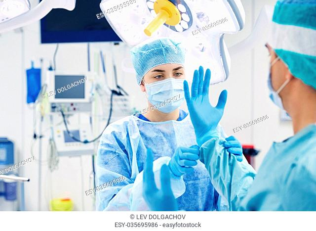 surgery, medicine and people concept - nurse assisting surgeon and helping with gloves in operating room at hospital