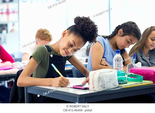 Confident junior high school girl student doing homework in classroom