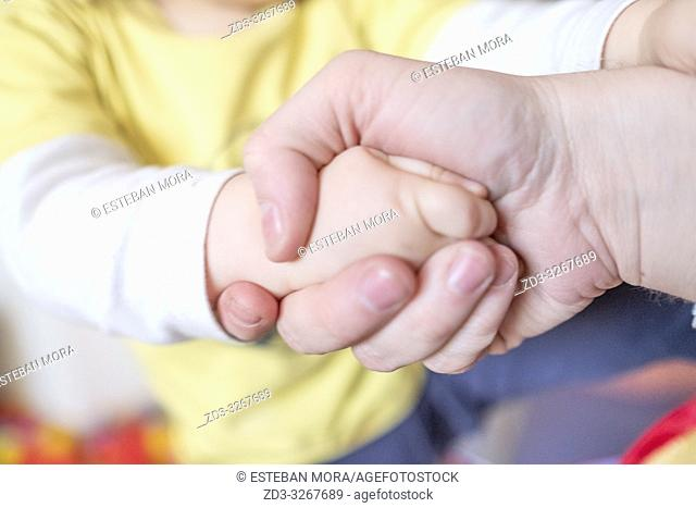 dad's hand holding and helping baby hand