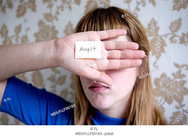 Student showing her hand, a note with the word fear on her hand