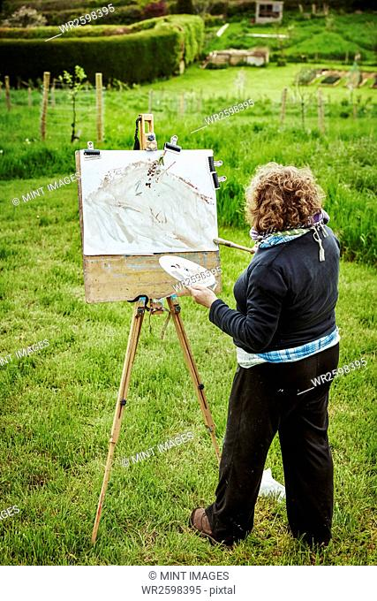 A woman artist standing outdoors at an easel, applying paint on paper with a brush