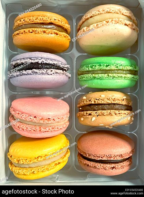 a group of colorful macarons stacked in a plastic package. Meringue-based dessert