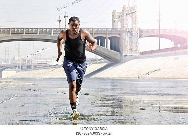 Young man speed running through city river
