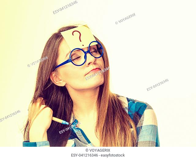 Thinking woman with big nerdy eyeglasses and question mark on forehead, on beige bright. Creating new idea, studying and education concept