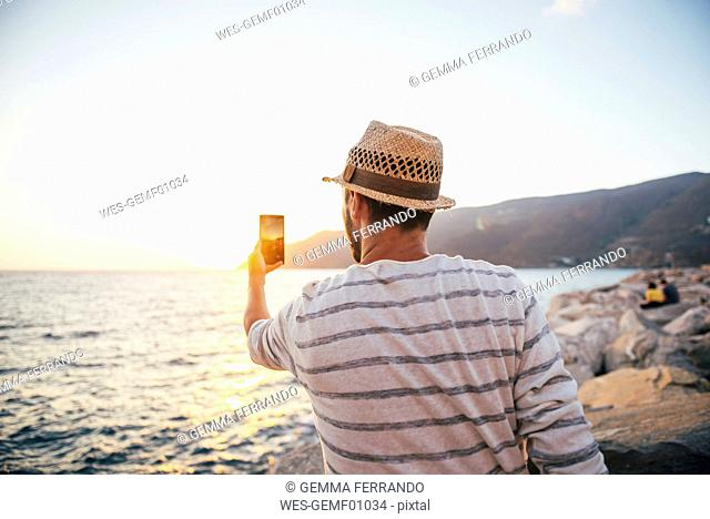 Greece, Cylcades Islands, Amorgos, man taking pictures of the sunset with a smartphone next to the sea