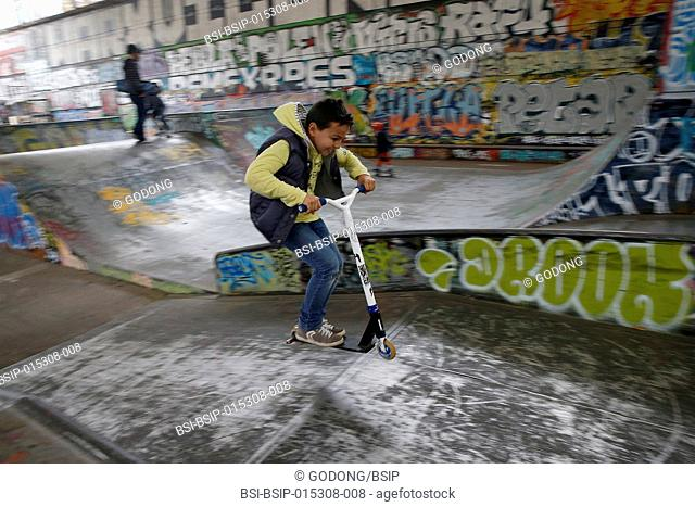 10-year-old boy riding a scooter in a skate park