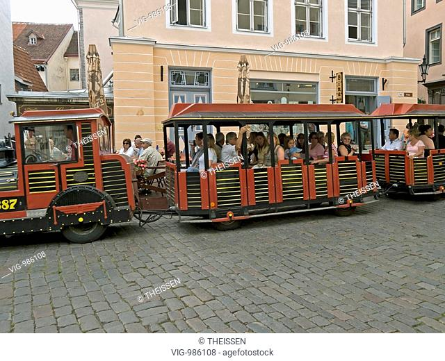 tourists in a street tram by sightseeing tour through the old town of Tallinn, Estonia. - 02/08/2008