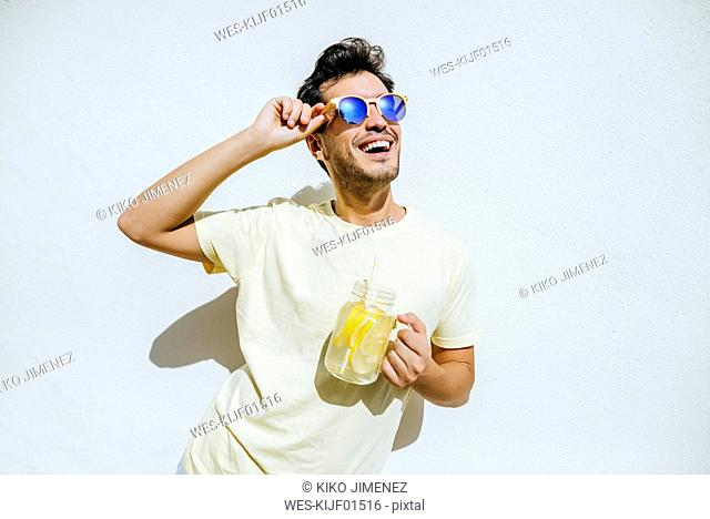 Young an with sunglasses and lemonade in front white wall