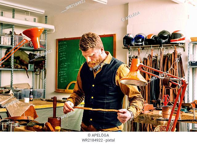 Male worker analyzing belt in workshop