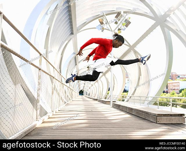 Sportsman doing the split while jumping on walkway