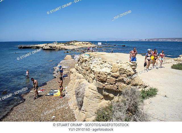 Bathers and sunbathers enjoy a pebble beach on the island of Tabarca Spain
