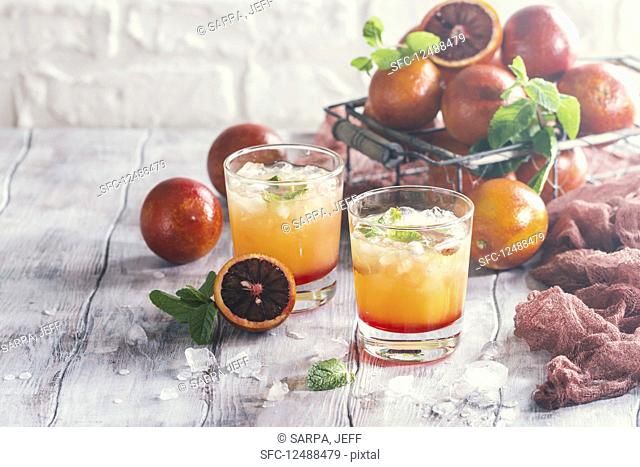 Alcohol tequila sunrise cocktail with red orange, ice and mint