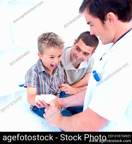 Doctor bandagins a child's arm who is yelling