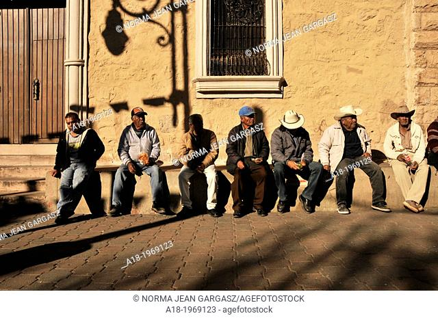 Men sit at a plaza in Nogales, Sonora, Mexico, across the border from Nogales, Arizona, USA