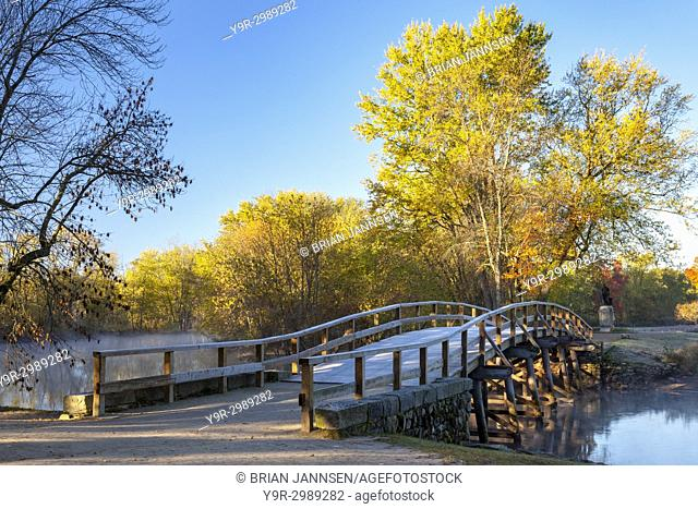 Autumn color in the maple trees at dawn over the Old North Bridge, Concord, Massachusetts, USA
