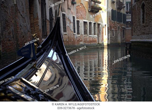 view from gondola on canal in Venice, Italy, bend up ahead, peeling building walls, shaft of light on building and reflected in water
