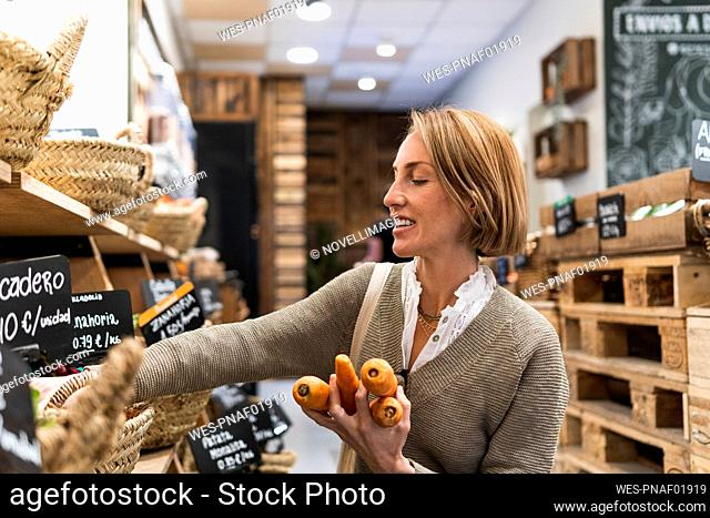 Blond woman collecting carrots in supermarket