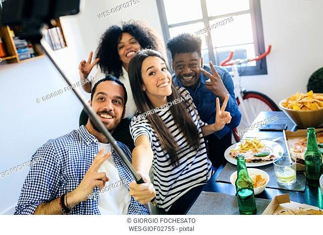 Group of friends posing for a selfie at dining table at home