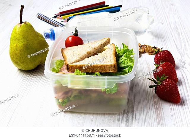 Healthy school lunch box with notebook and color pencils on white wooden background. Side view. Closeup