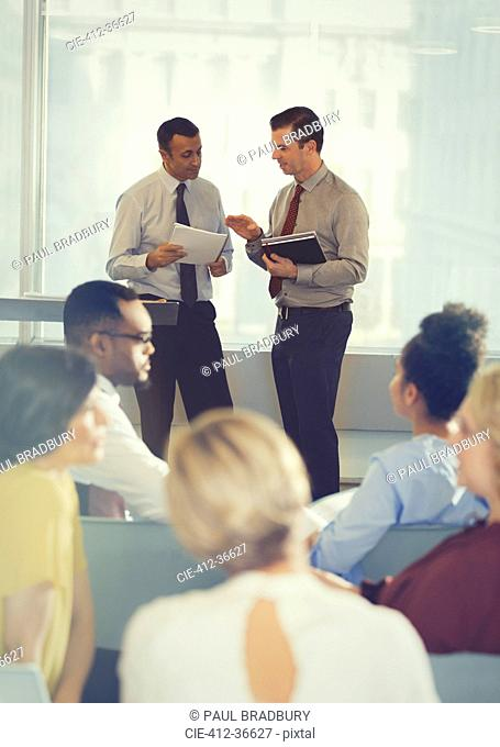 Businessmen talking in conference audience