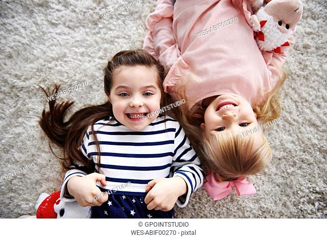 Portrait of two grinning little sisters lying on the carpet