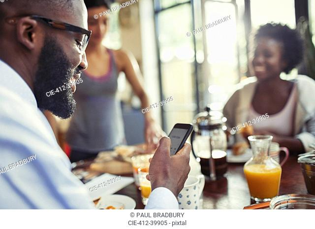 Young man texting with smart phone at kitchen table
