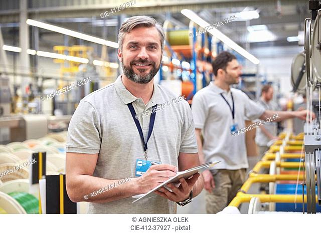 Portrait smiling, confident male supervisor with clipboard in fiber optics factory