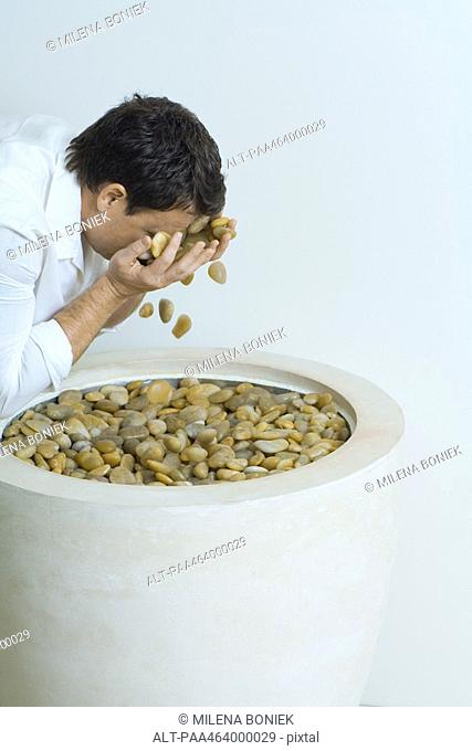 Man splashing face with pebbles, cropped, side view